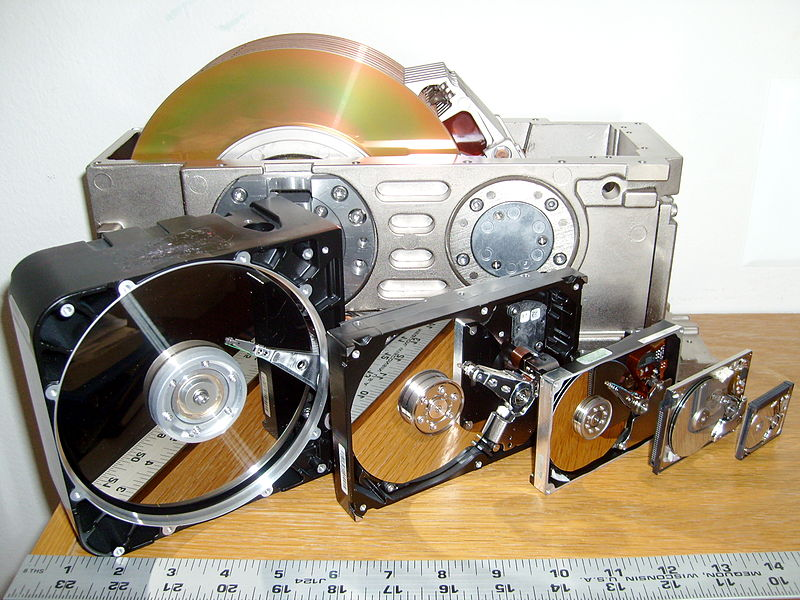 Six hard disk drives with cases opened showing platters and heads